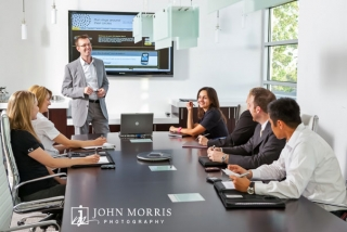 A CEO leads a discussion with a group of executives in a modern conference room during a commercial photo shoot.