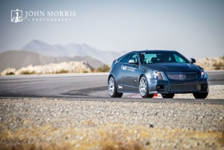 A sleek, black Cadillac races out of a tight corner during a commercial shoot at a test track in Nevada.