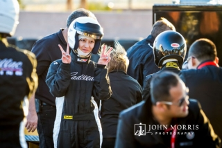 A female driver, wearing full racing gear and helmet gives the thumbs up during a commercial photo shoot.
