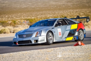 A Cadillac prototype race car maneuvers through a tight corner on a desert test track in Nevada.