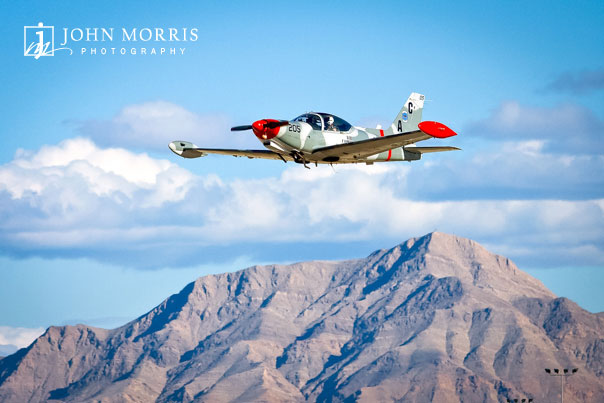 A small fighter training aircraft is used by a commercial company fly's low over Nevada mountains.