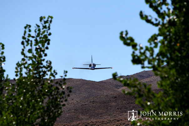 A private jet soars just over the tree tops at high speed during an avionics show in Reno, NV.