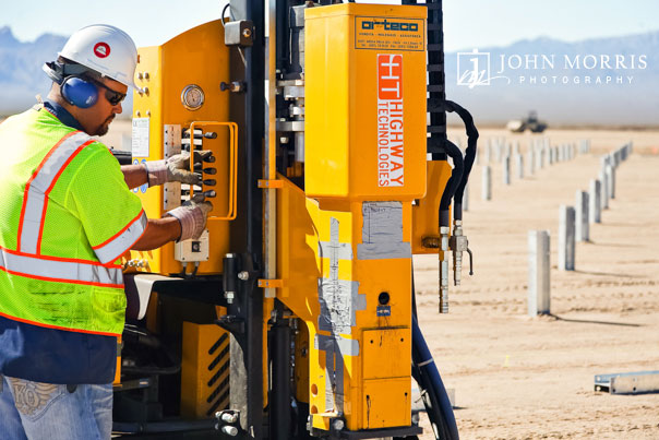 A solar panel construction worker prepares heavy equipment during a commercial photo shoot for a solar power company.