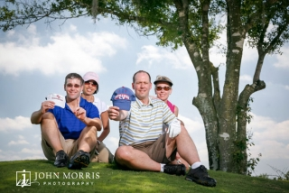 Four golfers seated under and tree and posing for the camera during a corporate golf outing.