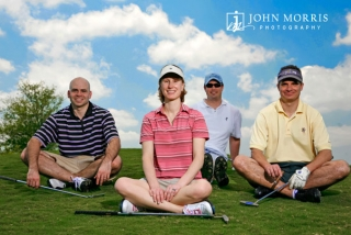 Four golfers posing for the camera on a golf course sitting yoga style for a corporate event.