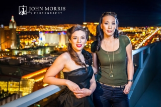 In a professional lit commercial photo, poker players Amanda Musumeci and Evelyn Ng pose high above the nighttime Vegas Strip.