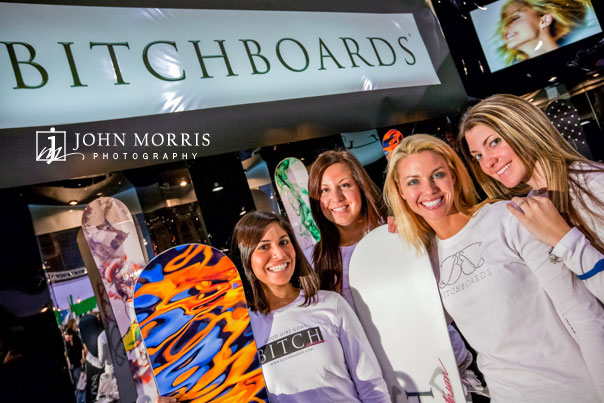 Four women exectives in casual snow board apparel pose in front of there exhibit booth for an editorial photo shoot.