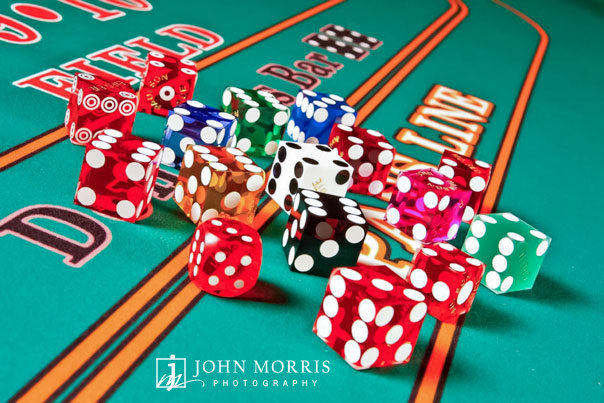 A variety of colorful gaming dice, displayed on a craps table for the purpose of a commercial product catalog.