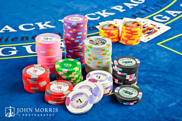 A variety of colorful poker chips, displayed against a blue blackjack table as part of a product photo shoot for a commercial company.
