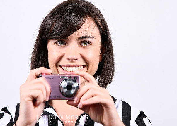 Fashion model, in studio against a white background, posing for the camera and holding a small compact camera for a product shoot.