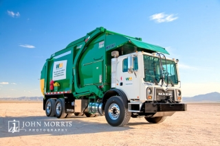 Giant green Waste Management Truck, modeled in the desert for a commercial, industrial photo shoot.