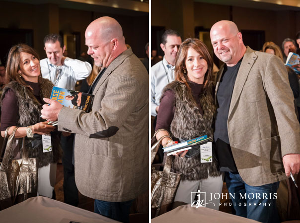 Rick Harrison, signs a book and poses with an attendee during a corporate event.
