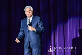Comedian Jay Leno, delivers a monologue to during the entertainment portion of a corporate event.