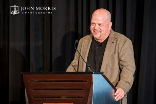 Pawn star, Rick Harrison, smiles from behind a podium while giving a presentation during a corporate event.