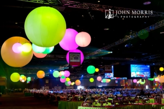 Giant, colorful globes, suspended from the cieling of a massive arena provide a fun and elegant atmosphere above a thousand exquisitely decorated tables in anticipation of a gala corporate event.