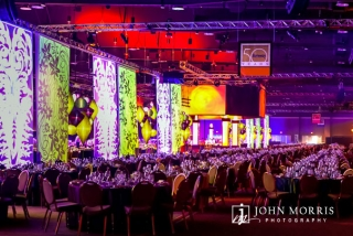 A massive, elaborated decorated arena is filled with thousands of exquisitely decorate tables in anticipation of a gala event honoring attendees during a corporate event.