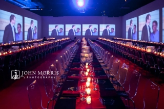 Longs rows of beautiful set tables, surrounded by a dazzling display of big screens, awaits awards winners and attendees before a corporate awards dinner.
