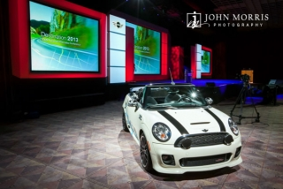 An white automobile highlights an elaborate stage set up for an upcoming keynote during a corporate event.