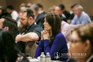 Woman listens intently from her seat to a presentation during a corporate breakout session