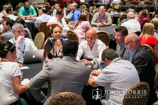 During a corporate breakout session, professionals sit around round tables and discuss important topics.