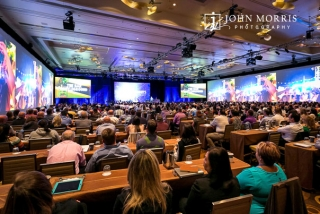 A crowded conference room, full of attendees, surrounded in a dazzling display of big screens, listen intently to a presentation during a corporate event.