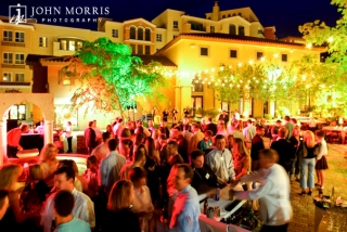 An outdoor venue, with a greek island feel, is bathed with light and full of happy attendees during a networking event.