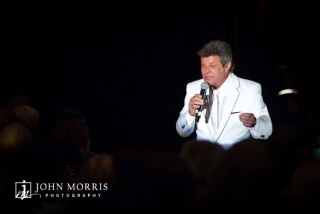 Frankie Avalon is isolated on stage in dramatic fashion from a single spotlight as he performs for an audience during a convention.