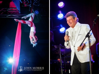 Frankie Valley performs on stage for an audience, as a talented trapeze artist dangles from colorful silk ropes during a conference.