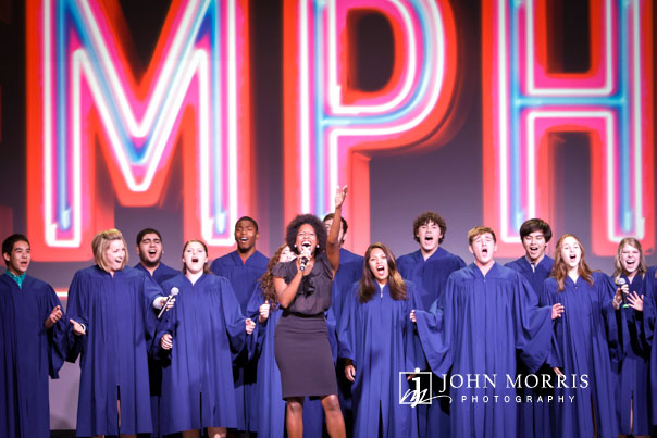 A choir, on stage, joyously belts out background vocals as an energetic singer raises her hand towards a crowd of attendees during a convention