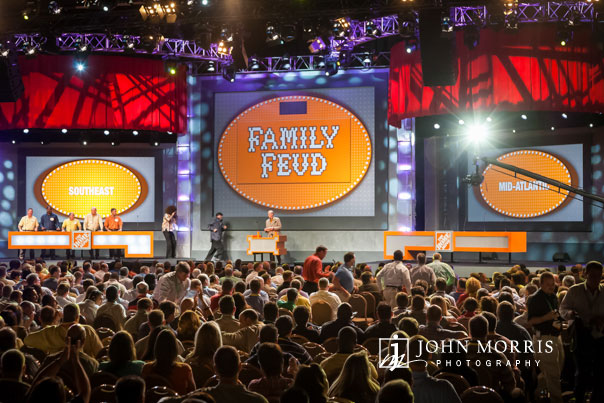 A capacity crowd of attendees pack a convention hall to watch and participate in a mock Family Feud entertainment segment of a corporate event.