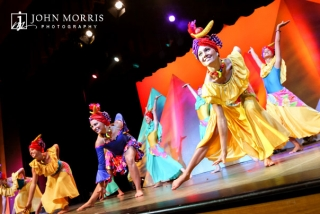 Team of dancers in very colorful costumes, dance with high energy on stage for an audience during a corporate event.