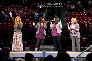 Four women, members of a vocal group, passionately perform a song on stage for large audience during a conference.