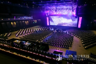 Wide and upper level view of a large arena and stage professionally decorated and prepared by an event company for a corporate event.