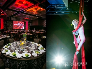 A trapeze artists gracefully hangs from silk material falling from the ceiling during the entertainment portion of a corporate awards dinner.