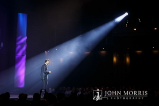 An executive delivers a keynote speech to his audience and is dramatically spotlighted, on stage, from a single light source