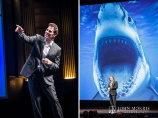 A giant image of a great white shark, projected on a massive screen behind a speaker, creates a comical but strong impression on the audience during a speech at a conference.