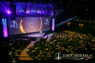 The spotlight shines on a CEO as he delivers his keynote speech to a crowded arena as seen from the upper levels.