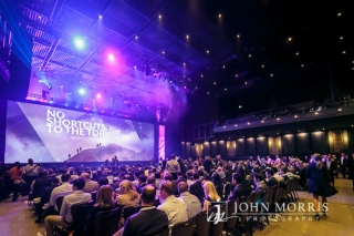 Wide angle view of a brilliantly lit stage and venue filled to capacity with attendees during a keynote speech.