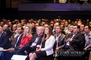 Audience of attendees in professional business attire listening inventively to a keynote speaker during a conference.