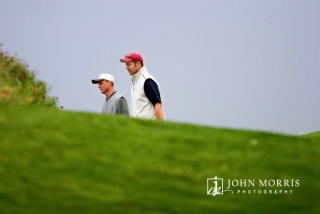 Two golfers, participating in a corporate golf outing, head towards the next green partially hidden by a mound of grass.