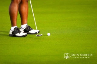 A closeup of a golfers shoes, and his putter head as he strikes a golf ball on an immaculate putting surface during a corporate outing.
