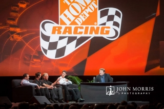 Joe Gibbs and Joey Logano join Comedian Frank Caliendo on stage during a talk to attendees at a corporate event.