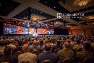 A packed convention hall full of attendees listening to a presentation during a keynote speech.