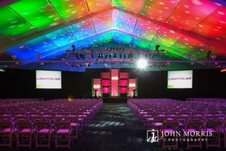 Large, spacious tent and stage are dramatically lit and converted to a conference hall for a corporate event.