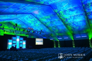 Large venue tent and stage are dramatically lit in preparation for keynote and corporate event.