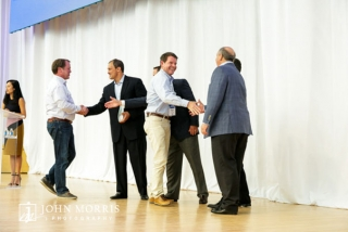Business shaking hands and accepting awards on stage during a corporate awards ceremony.