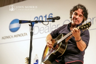 John Oates, on stage, playing guitar for an intimate crowd of attendees during a corporate event.