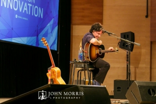 John Oates performing on stage, unplugged, with guitar for a corporate event attendees in an intimate setting.