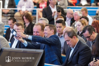 Attendees in business attire, taking a selfie while seated in the audience before the keynote speech at a corporate event.