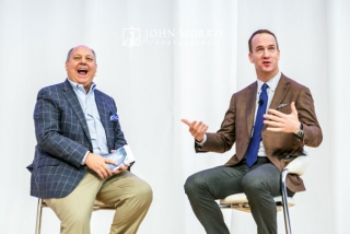 Peyton Manning, seated on stage and sharing a laugh during a question and answer session at a corporate keynote event.